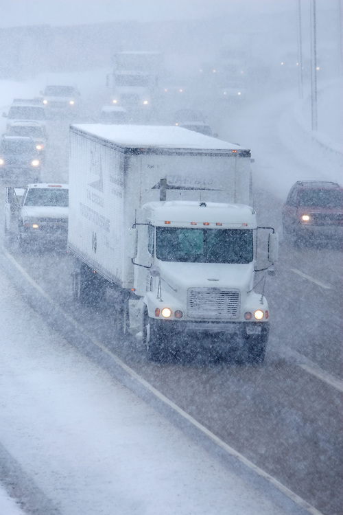 white-truck-on-interstate-highway-in-snow